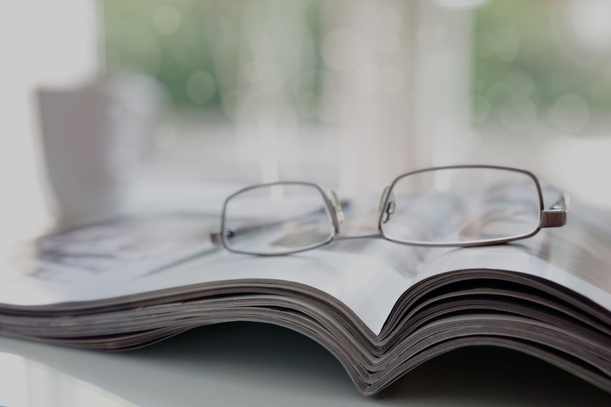 Magazines on a desk with reading glasses